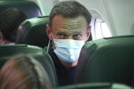 Alexei Navalny sits on the plane prior to a flight to Moscow, at the Airport Berlin Brandenburg (BER) in Schoenefeld, near Berlin, Germany, Sunday, Jan. 17, 2021. Leading Kremlin critic Alexei Navalny flew home to Russia on Sunday after recovering in Germany from his poisoning in August with a nerve agent. (AP Photo/Mstyslav Chernov)
