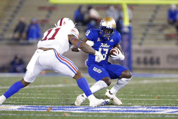 Tulsa wide receiver Josh Johnson (13) tries to avoid SMU safety Chevin Calloway (11) after a catch during the second half of an NCAA college football game in Tulsa, Okla., Saturday, Nov. 14, 2020. (AP Photo/Joey Johnson)