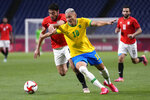 Egypt's Akram Tawfik, left, and Brazil's Richarlison battle for the ball during a men's quarterfinal soccer match at the 2020 Summer Olympics, Saturday, July 31, 2021, in Saitama, Japan. (AP Photo/Martin Mejia)