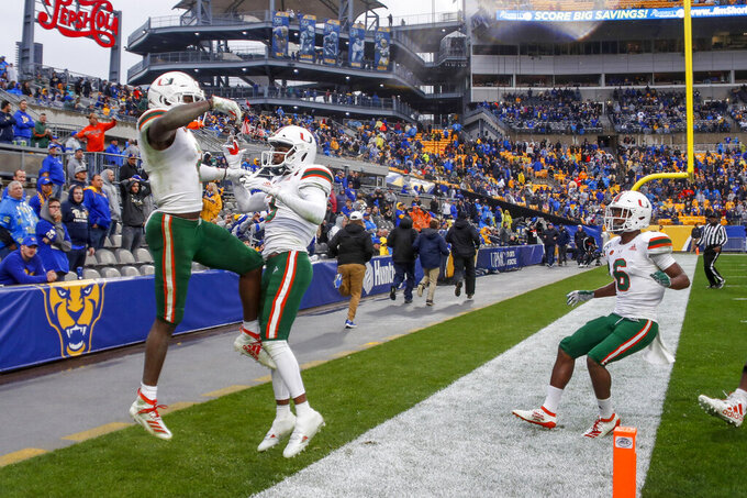 Miami wide receiver K.J. Osborn, left, celebrates with Mike Harley, center, and Mark Pope (6) after catching pass and scoring a touchdown against Pittsburgh during the fourth quarter of an NCAA college football game, Saturday, Oct. 26, 2019, in Pittsburgh. Miami won 16-12. (AP Photo/Keith Srakocic)