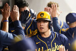 Milwaukee Brewers' Luis Urias celebrates with teammates after hitting a two-run home run during the fourth inning against the Cleveland Indians in a baseball game Friday, Sept. 10, 2021, in Cleveland. (AP Photo/Tony Dejak)