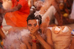A Hindu holy man smokes as he waits to register for the annual pilgrimage to the Amarnath cave shrine in Jammu, India, Monday, July 1, 2019. Thousands of Hindu pilgrims began the arduous trek to an icy Himalayan cave in disputed Kashmir on Monday, with tens of thousands of Indian government forces guarding roads and mountain passes. (AP Photo/Channi Anand)