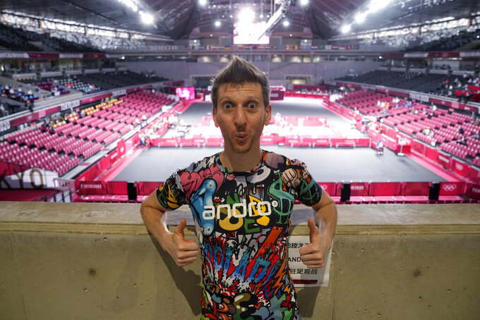 Adam Bobrow, lead commentator for the International Table Tennis Federation, poses for a photograph during the table tennis men's team semifinal between Germany and Japan at the 2020 Summer Olympics, Wednesday, Aug. 4, 2021, in Tokyo. Bobrow, the Voice of Table Tennis, possesses an arsenal of tricky spin shots, captured on YouTube and watched by millions, that can leave even good opponents gape-mouthed and then, as the wildness of what they've seen sinks in, delighted. What he really likes, though, is to travel the world as a sort of ambassador for the sport. (AP Photo/Kin Cheung)