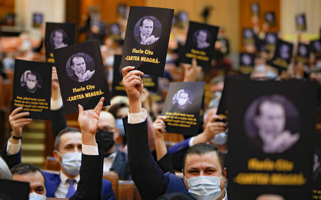 Opposition members of parliament hold leaflets showing prime minister-designate Florin Citu, reading
