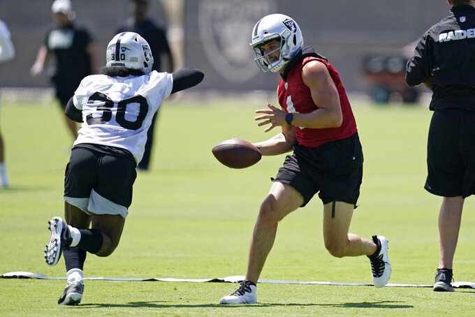 Las Vegas Raiders quarterback Derek Carr (4) looks to hand off to running back Jalen Richard (30) during NFL football practice Wednesday, June 2, 2021, in Henderson, Nev. (AP Photo/John Locher)