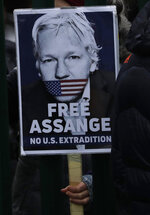 A supporter hold a placard which reads 'Free Assange' as she protests against the extradition of Wikileaks founder Julian Assange outside Belmarsh Magistrates Court in London, Monday, Feb. 24, 2020. The U.S. government and WikiLeaks founder Julian Assange will face off Monday in a high-security London courthouse, a decade after WikiLeaks infuriated American officials by publishing a trove of classified military documents. (AP Photo/Matt Dunham)