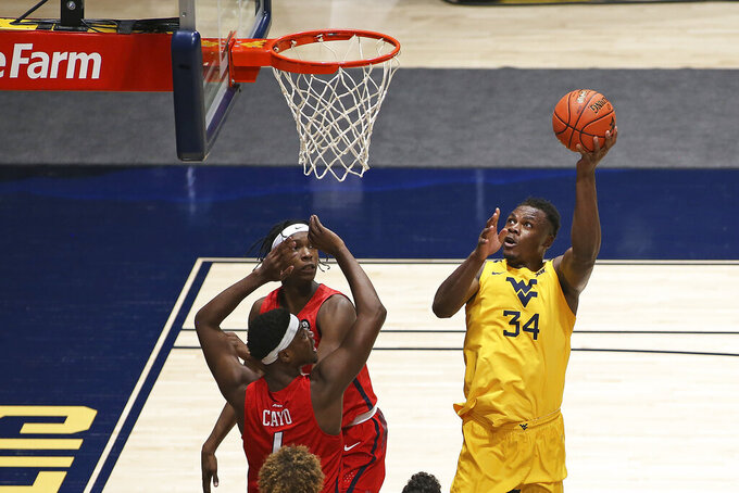 West Virginia forward Oscar Tshiebwe (34) shoots while defended by Richmond forwards Nathan Cayo (front) and Souleymane Koureissi (behind) during the first half of an NCAA college basketball game Sunday, Dec. 13, 2020, in Morgantown, W.Va. (AP Photo/Kathleen Batten)