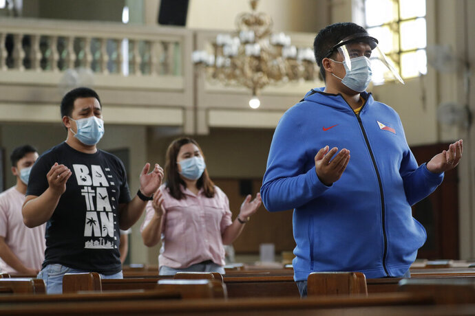 Parishioners wearing masks as a measure to prevent the spread of COVID19 pray during a Mass at the Our Lady of Consolation Parish on Sunday, Aug. 2, 2020, in Quezon city, Philippines. Coronavirus infections in the Philippines continues to surge Sunday as medical groups declared the country was waging