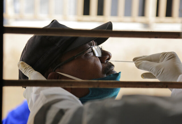 A health worker takes a nasal swab sample to test for COVID-19 at an urban health centre in Ahmedabad, India, Thursday, Sept. 10, 2020. India's coronavirus cases are now the second-highest in the world and only behind the United States. (AP Photo/Ajit Solanki)