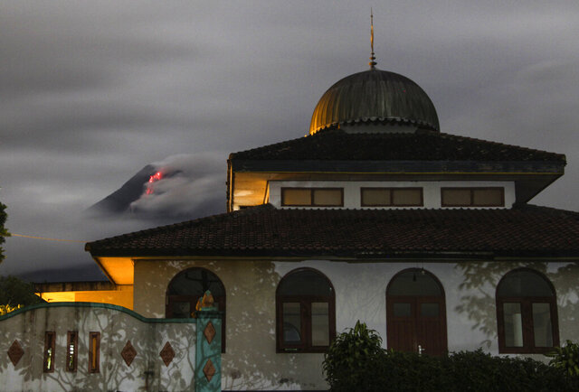 Hot lava runs down from the crater of Mount Merapi, partially seen behind a mosque in Sleman, Indonesia, late Tuesday, Jan. 26, 2021. The country's most active volcano erupted Wednesday with a river of lava and searing gas clouds flowing 1,500 meters (4,900 feet) down its slopes. (AP Photo/Slamet Riyadi)