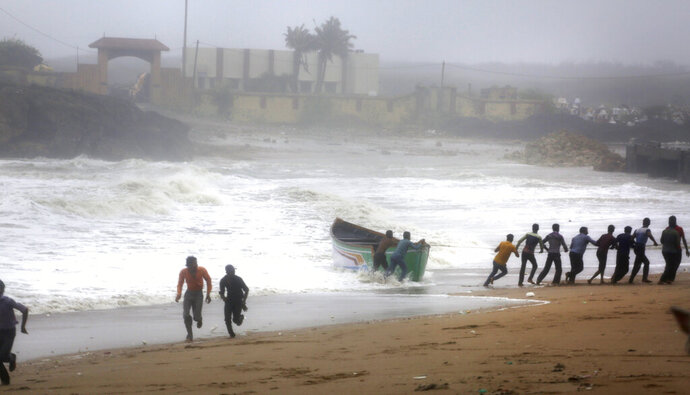 People try to pull back a fishing boat that was carries away by waves on the Arabian Sea coast as others run to take shelter in Veraval, Gujarat, India, Thursday, June 13, 2019. Authorities have evacuated nearly 300,000 people from India's western coastline ahead of a very severe cyclone that's expected to make landfall as the year's second major storm. The India Meteorological Department says Cyclone Vayu, named after the Hindi word for wind, could glance the western state of Gujarat Thursday afternoon before returning to sea. (AP Photo/Ajit Solanki)