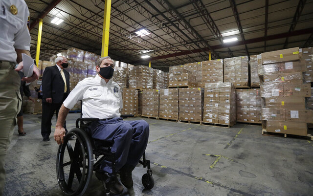 Texas Gov. Greg Abbott, left,, and other officials visit a Texas Division of Emergency Management Warehouse filled with Personal Protective Equipment, Tuesday, Aug. 4, 2020, in San Antonio. (AP Photo/Eric Gay)