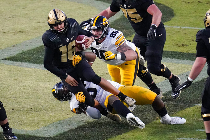 Purdue quarterback Aidan O'Connell (16) is sacked by Iowa defensive linemen Jack Heflin (96) and Chauncey Golston (57) during the fourth quarter of an NCAA college football game in West Lafayette, Ind., Saturday, Oct. 24, 2020. (AP Photo/Michael Conroy)