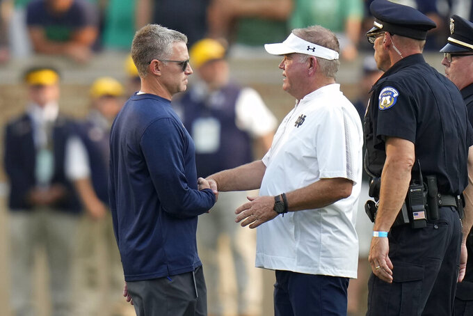 Notre Dame head coach Brian Kelly, right, shakes hands with Toledo head coach Jason Candle after an NCAA college football game in South Bend, Ind., Saturday, Sept. 11, 2021. Notre Dame won 32-29. (AP Photo/AJ Mast)