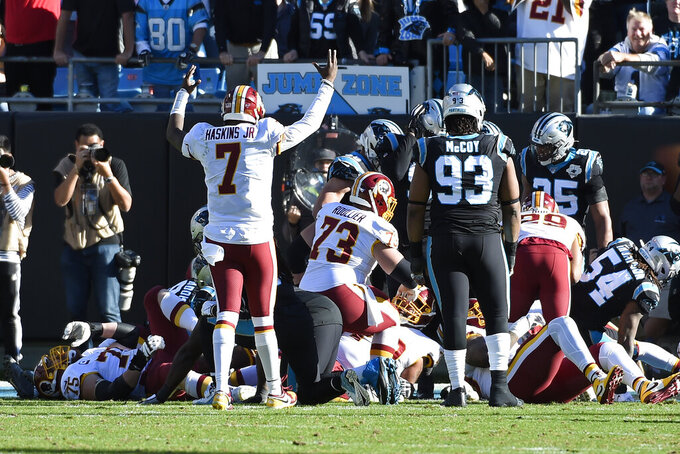 Washington Redskins quarterback Dwayne Haskins (7) signals for a touchdown following running back Derrius Guice's score against the Carolina Panthers during the first half of an NFL football game in Charlotte, N.C., Sunday, Dec. 1, 2019. (AP Photo/Mike McCarn)