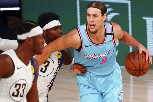 Miami Heat forward Kelly Olynyk (9) dribbles against Indiana Pacers guard Aaron Holiday (3) during the second half of an NBA basketball game Monday, Aug. 10, 2020, in Lake Buena Vista, Fla. (Kim Klement/Pool Photo via AP)