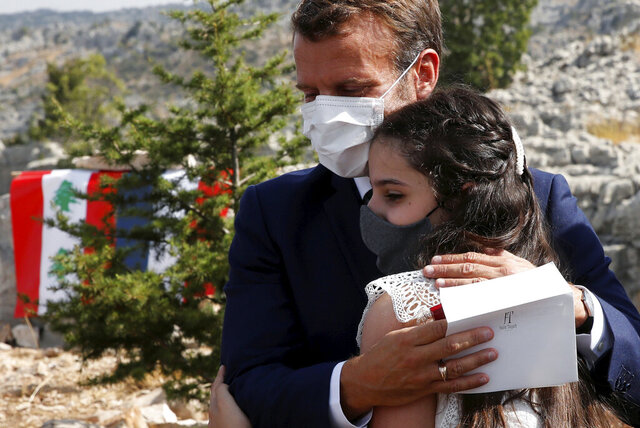 French President Emmanuel Macron hugs blast victim Tamara Tayah after planting a cedar with members of the NGO Jouzour Loubnan in Jaj, near Beirut, Tuesday Sept. 1, 2020. French President Emmanuel Macron returned to Lebanon on Monday, a country in the midst of an unprecedented crisis, for a two-day visit and a schedule packed with events and political talks aimed at charting a way out for the country. (Gonzalo Fuentes/Pool via AP)