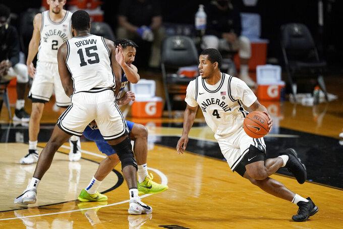 Vanderbilt guard Jordan Wright (4) drives around teammate Clevon Brown (15) in the second half of an NCAA college basketball game against Kentucky Wednesday, Feb. 17, 2021, in Nashville, Tenn. (AP Photo/Mark Humphrey)