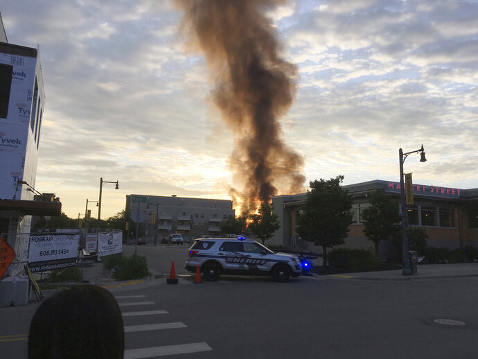 A large plume of smoke from a massive fire is seen in Sun Prairie, Wis., Tuesday, July 10, 2018. Witnesses said the fire broke out after a loud boom Tuesday night shook the community. Police blocked off downtown streets from traffic and onlookers. (AP Photo/Todd Richmond)