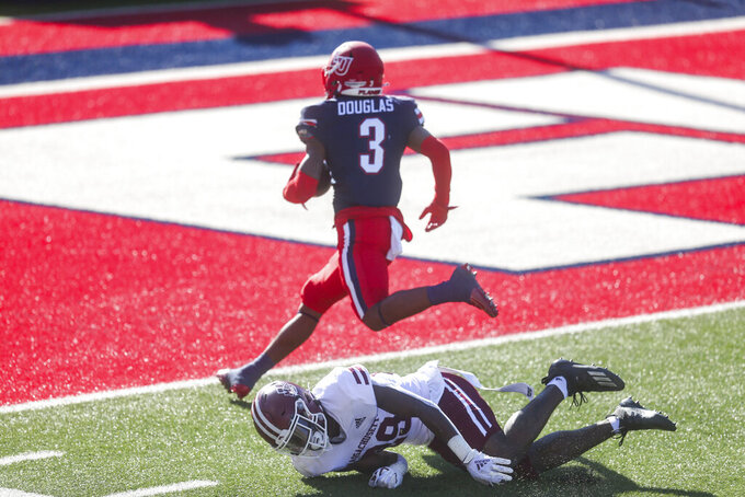 Liberty wide receiver Demario Douglas (3) scores a touchdown as he is defended by Massachusetts player Cody Jones (29) during the first half of a NCAA college football game on Friday, Nov. 27, 2020, at Williams Stadium in Lynchburg, Va. (AP Photo/Shaban Athuman)