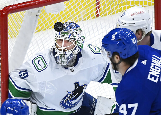 Vancouver Canucks goaltender Braden Holtby (49) eyes the loose puck against Toronto Maple Leafs forward Pierre Engvall (47) during the first period of an NHL hockey game, Thursday, April 29, 2021 in Toronto. (Nathan Denette/Canadian Press via AP)