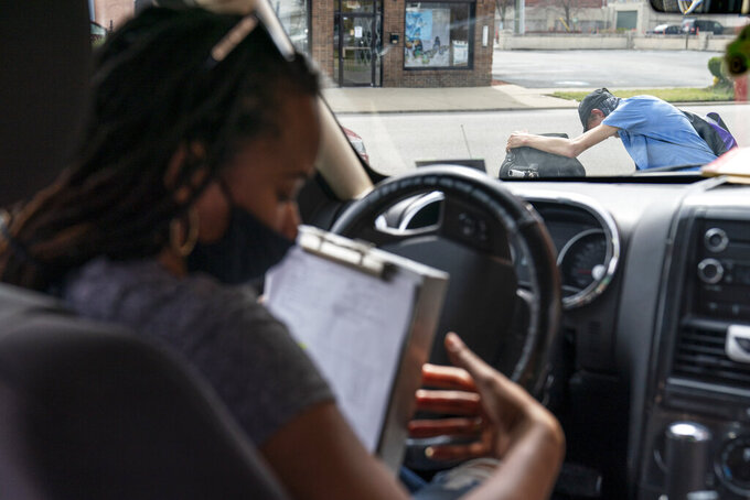 Larrecsa Cox, who leads the Quick Response Team, sits in her car with a list of people to visit after giving a man on the street a supply of the overdose reversal medication naloxone to carry on him in Huntington, W.Va., Wednesday, March 17, 2021. The team tries to track down everyone who overdosed, searching for them in abandoned houses and tent encampments on the river, at half-million-dollar homes on the golf course, out on the rural roads that wind toward the mountains. If the people they find are ready for treatment, they get them there. If they aren't, they try to help them survive in the meantime. (AP Photo/David Goldman)