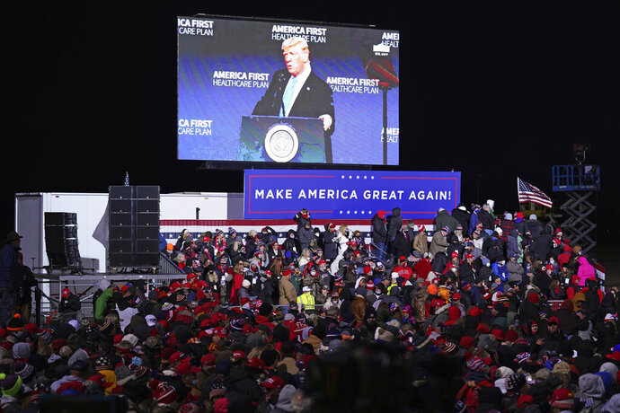 An image of President Donald Trump is projected on a large screen as supporters wait for his arrival to a campaign rally in Omaha, Neb., Tuesday, Oct. 27, 2020. (AP Photo/Nati Harnik)