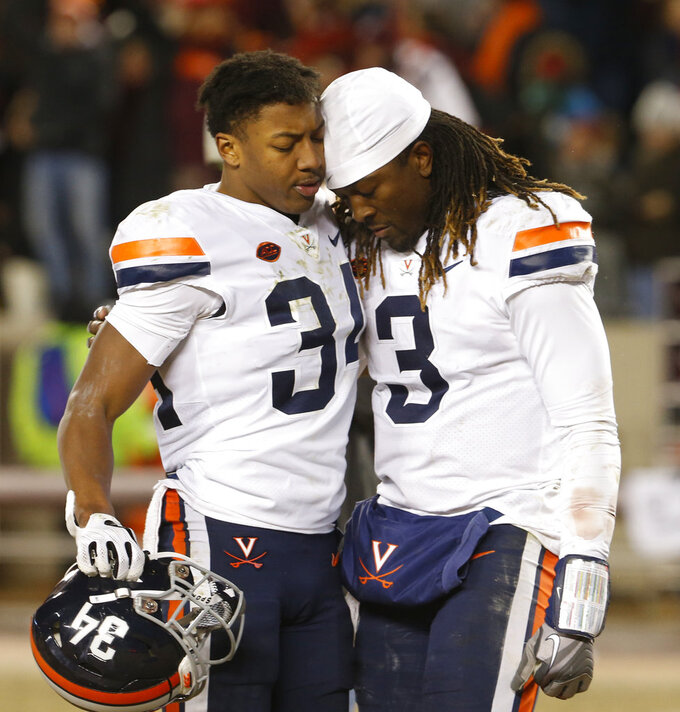 Virginia quarterback Bryce Perkins (3) is consoled by cornerback Bryce Hall (34) after an NCAA college football game against Virginia Tech in Blacksburg, Va., Friday, Nov. 23, 2018. Virginia Tech won 34-31. (AP Photo/Steve Helber)