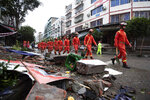 In this photo released by Xinhua News Agency, rescue workers walk near debris in the aftermath of an earthquake in Fuji Township of Luxian County in southwestern China's Sichuan Province, on Thursday, Sept. 16, 2021.An earthquake collapsed homes, killed some and injured others Thursday in southwest China's Sichuan province, state media reported. (Jiang Hongjing/Xinhua via AP)