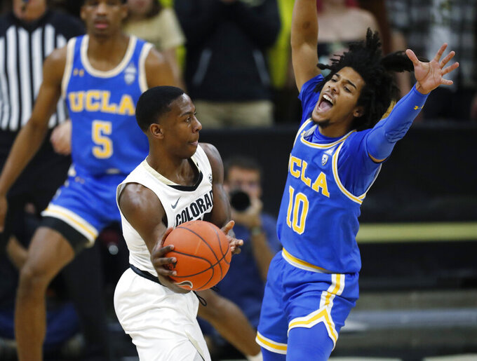 Colorado guard McKinley Wright IV, left, passes the ball as UCLA guard Tyger Campbell defends in the first half of an NCAA college basketball game Saturday, Feb. 22, 2020, in Boulder, Colo. (AP Photo/David Zalubowski)