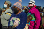 People affected by the coronavirus economic downturn, line up to receive food donations at the Iterileng informal settlement near Laudium, southwest of Pretoria, South Africa, Wednesday, May 20, 2020. (AP Photo/Themba Hadebe)