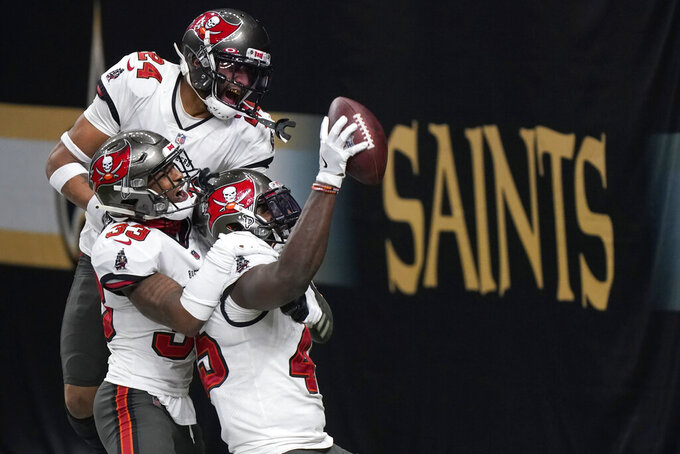 Tampa Bay Buccaneers inside linebacker Devin White, bottom right, celebrates after intercepting a pass with teammates Jordan Whitehead (33) and Carlton Davis (24) against the New Orleans Saints during the second half of an NFL divisional round playoff football game, Sunday, Jan. 17, 2021, in New Orleans. (AP Photo/Brynn Anderson)