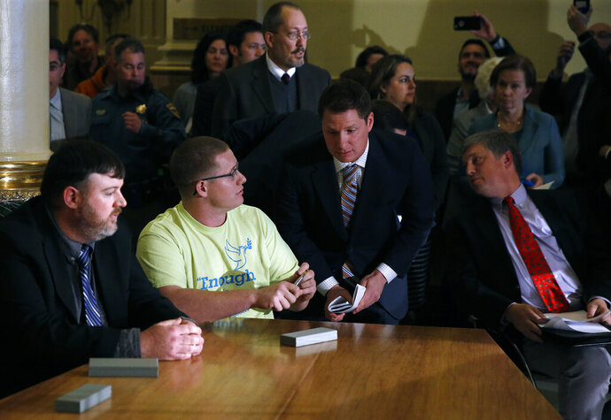 FILE - In this Dec. 19, 2016, file photo, Colorado elector Micheal Baca, second from left, talks with legal counsel after he was removed from the panel for voting for a different candidate than the one who won the popular vote, during the Electoral College vote at the Capitol in Denver. Colorado Secretary of State Wayne Williams, front right, looks on. On Tuesday, Aug. 20, 2019, the 10th U.S. Circuit Court of Appeals ruled that Williams violated the Constitution when he removed Baca from the panel. (AP Photo/Brennan Linsley, File)