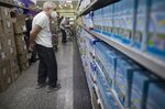 A man looks at the prices of milk at a supermarket in Caracas, Venezuela, Friday, June 4, 2021. Two years ago Venezuela stopped restricting transactions in dollars, which has largely ended shortages but has meant many Venezuelans, who are paid in bolivars, can't afford what's on those shelves. ( AP Photo/Ariana Cubillos)