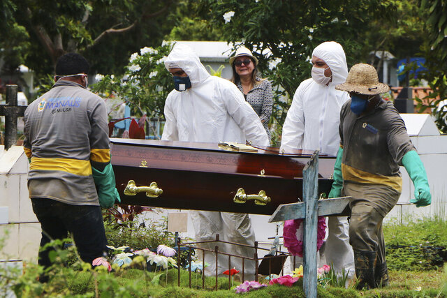 A relative stands at a distance during the burial of Robson de Souza Lopes at Parque Taruma cemetery in Manaus, Brazil, Tuesday, March 31, 2020. According to authorities at the Amazonas Health Secretary, the 43-year-old musician died Monday after being diagnosed with COVID-19. (AP Photo/Edmar Barros)