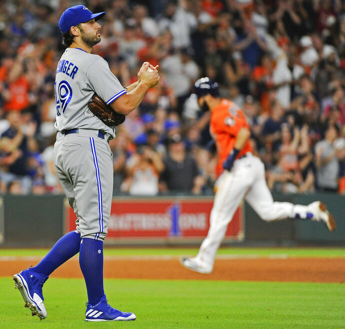 FILE - In this Aug. 4, 2017 file photo Toronto Blue Jays relief pitcher Mike Bolsinger, left, walks off the mound as Houston Astros' Marwin Gonzalez rounds the bases after hitting a three-run home run during the fourth inning of a baseball game in Houston. Bolsinger sued the Astros on Monday, Feb. 10, 2020 claiming their sign-stealing scheme contributed to a poor relief appearance August 2017 that essentially ended his big league career. (AP Photo/Eric Christian Smith, file)