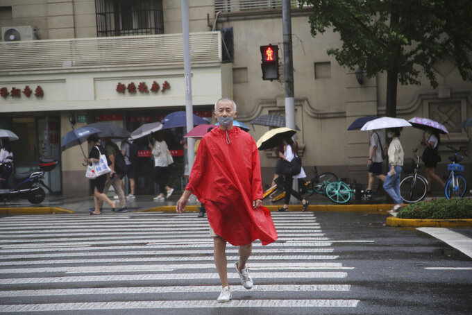 A resident wearing a mask and rain gear crosses the road in Shanghai, China, Tuesday, Sept. 14, 2021. Flights and train service were being canceled in Shanghai, China's largest city, as Typhoon Chanthu moved up the mainland coast Monday after bringing heavy rain and wind to Taiwan. (AP Photo/Chen Si)