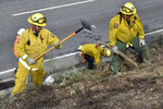 A fire prevention crew removes vegetation along California's Route 17 on Wednesday, Nov. 20, 2019, near Redwood Estates, Calif. Vehicle fires are a recurring problem in the area and authorities fear a blaze could quickly spread into nearby residential areas. (AP Photo/Matthew Brown)