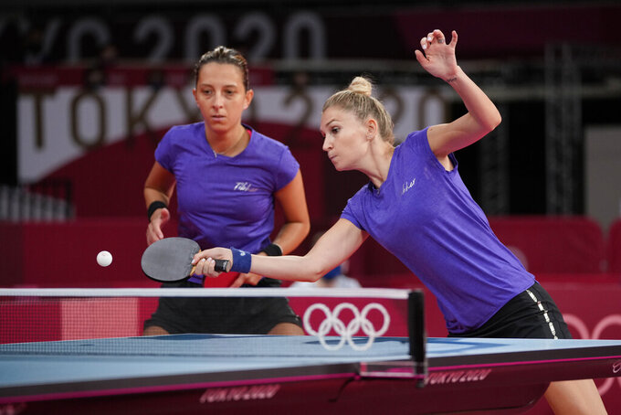 Romania's Elizabeta Samara, left, and Daniela Dodean compete during the table tennis women's team round of 16 against Egypt's Yousra Helmy and Farah Abdelaziz at the 2020 Summer Olympics, Sunday, Aug. 1, 2021, in Tokyo, Japan. (AP Photo/Kin Cheung)