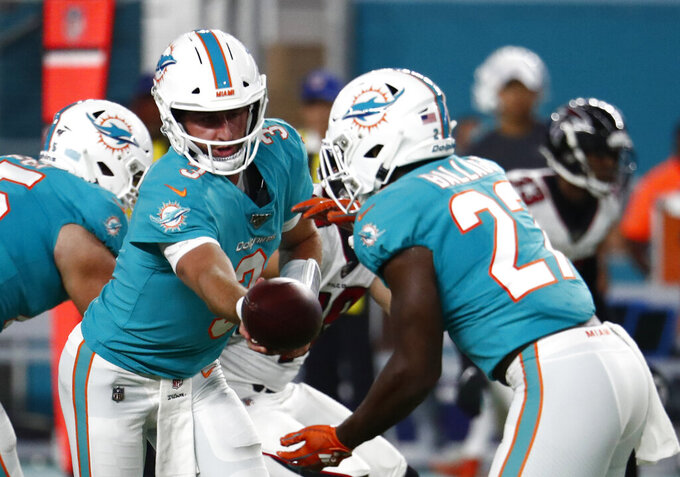 Miami Dolphins quarterback Josh Rosen, left, hands off to running back Kalen Ballage during the first half of the team's preseason NFL football game against the Atlanta Falcons, Thursday, Aug. 8, 2019, in Miami Gardens, Fla. (AP Photo/Brynn Anderson)