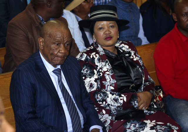 Lesotho's Prime Minister, Thomas Thabane, left, and his wife Maesaiah, right are seated in court, in Maseru, Monday, Feb. 24, 2020.  Thabane appeared in court on Monday over the murder of his estranged wife after a weekend in which he was said to be receiving emergency medical care in South Africa. The matter was deferred to the High Court and the prime minister was not formally charged. (AP Photo)