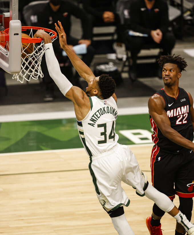 Milwaukee Bucks forward Giannis Antetokounmpo (34) dunks as Miami Heat forward Jimmy Butler (22) watches during the second half of Game 2 of their NBA basketball first-round playoff series Monday, May 24, 2021, in Milwaukee. (AP Photo/Jeffrey Phelps)