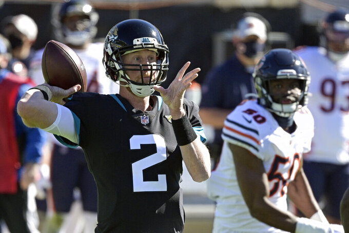 Jacksonville Jaguars quarterback Mike Glennon (2) throws a pass as he is rushed by Chicago Bears linebacker Barkevious Mingo (50) during the first half of an NFL football game, Sunday, Dec. 27, 2020, in Jacksonville, Fla. (AP Photo/Phelan M. Ebenhack)
