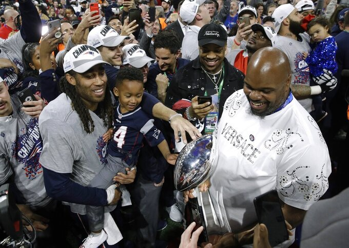 New England Patriots' Stephon Gilmore, left, celebrates alongside former Patriots star Vince Wilfork, right, holding the trophy after the NFL Super Bowl 53 football game against the Los Angeles Rams, Sunday, Feb. 3, 2019, in Atlanta. The Patriots won 13-3. (AP Photo/Patrick Semansky)