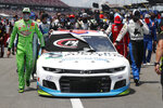 FILE - In this June 22, 2020, file photo, NASCAR drivers Kyle Busch, left, and Corey LaJoie, right, join other drivers and crews as they push the car of Bubba Wallace to the front of the field prior to the start of the NASCAR Cup Series auto race at the Talladega Superspeedway in Talladega Ala. The Cup Series returns to Talladega on Sunday. (AP Photo/John Bazemore, File)