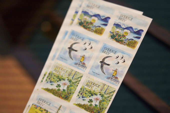 Swedish teenage environmental activist Greta Thunberg appears on a postal stamp in her native Sweden that is part of a series focusing on the environment, in Stockholm, Wednesday, Jan. 13, 2021. One of the stamps features teenage environmental activist Greta Thunberg in her trademark yellow raincoat with her braid blowing in the wind and standing a top a hill. (AP Photo/David Keyton)