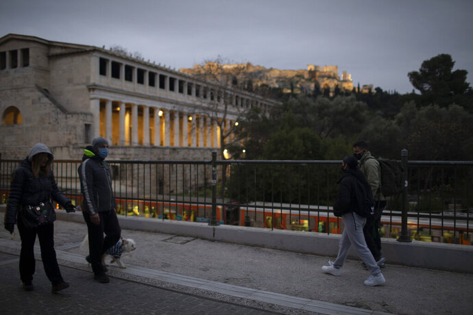 Pedestrians wearing protective face masks walk past the ancient Agora, in Athens, on Friday, Jan. 15, 2021. Greece's prime minister says the country's retail sector might begin to gradually reopen next week, if the scientists advising the government on the coronavirus pandemic recommend it is safe to do so today. (AP Photo/Petros Giannakouris)