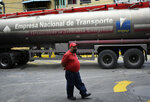 A worker wearing a face mask amid the new coronavirus pandemic waits while a tanker truck supplies gasoline to a state oil company gas station in Caracas, Venezuela, Sunday, May 31, 2020. After decades of being the cheapest gasoline in the world, Venezuelan President Nicolas Maduro indicates that as of next Monday a new pricing scheme will be imposed on some 200 stations. (AP Photo/Matias Delacroix)