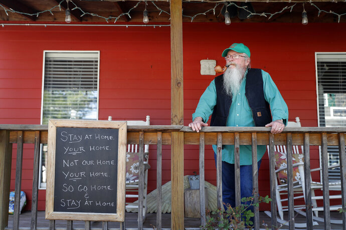 In this Tuesday, April 7, 2020 photo, Mayor Phil Stang stands on the front porch of his home with a friendly message to anyone passing by in Kimmswick, Mo. The tiny town along the banks of the Mississippi River, normally bustling with out-of-town visitors this time of year, is virtually empty as the economic ravages of the coronavirus has shuttered shops and restaurants in the community. (AP Photo/Jeff Roberson)