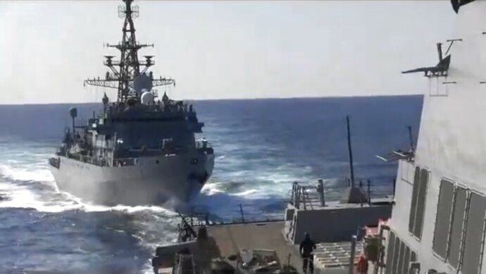 """This photo provided bythe U.S. 5th Fleet, shows a Russian Navy ship approaching an American warship in the North Arabian Sea, on Thursday, Jan. 9, 2020.  A spokesman for U.S. 5th Fleet said Friday that the USS Farragut was conducting routine operations Thursday and sounded five short blasts to warn the Russian ship of a possible collision. He said the USS Farragut asked the Russian ship to change course and the ship initially refused but ultimately moved away. Even though the Russian ship moved away, the Navy spokesman said the delay in shifting course """"increased the risk of collision.""""  (U.S. 5th Fleet via AP)"""